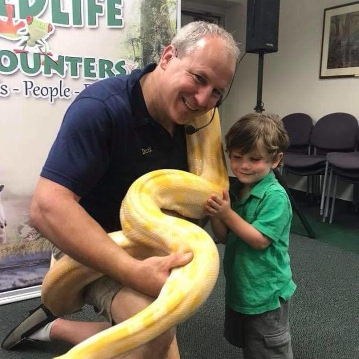 Derek handling a large snake during a presentation with young kids.