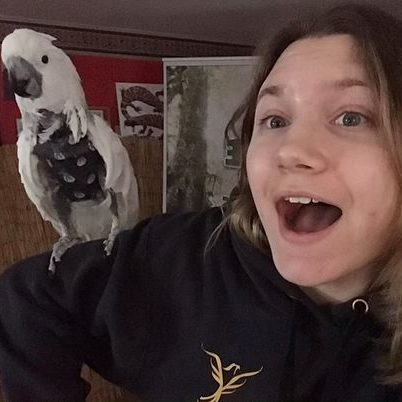 Riley with a cockatoo on her shoulder